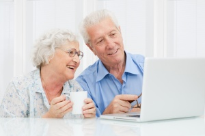 Happy elder couple enjoy together at laptop computer